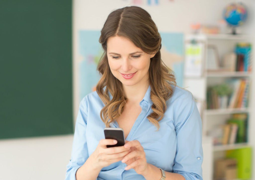 teacher in classroom looking at mobile phone