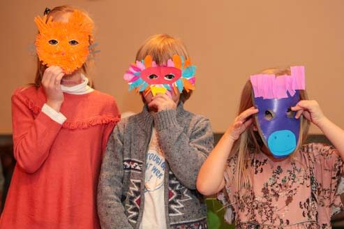 Young students holding crafted paper masks over their faces