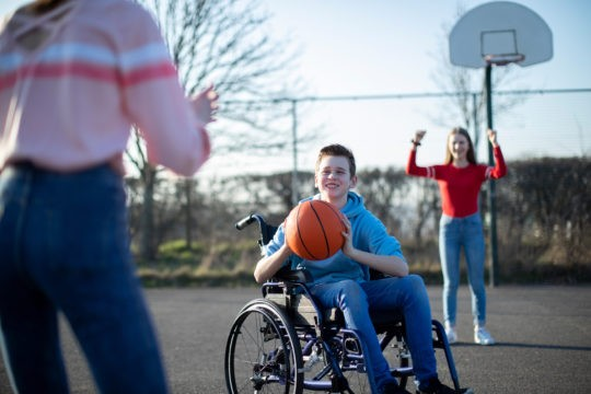 Young boy in a wheelchair playing basketball with two girls.