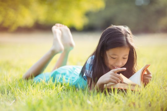 Young girl lying in the grass reading a book.