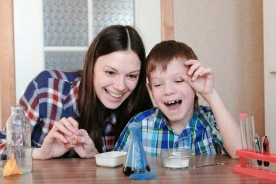 Mom and young son doing a science experiment at home.