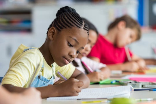 Young girl writing in a notebook among other students in a classroom.