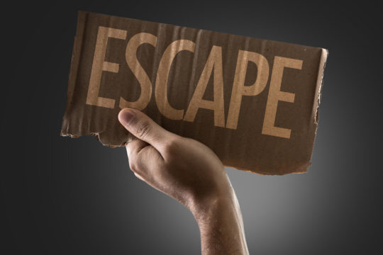 Hand holding up a cardboard sign reading 'escape.'