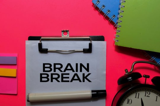 'Brain Break' written on a clipboard surrounded by notebooks and a clock.