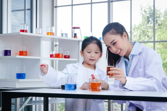 Female teacher and child using look a measuring cups filled with colored liquid