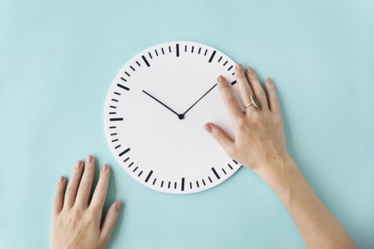 A clock with a lady's hand moving the hands