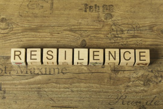 The word 'Resilience' spelled out in blocks on a wooden table