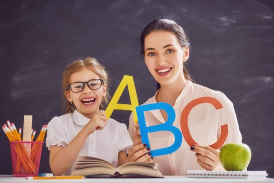 Young girl holding up letters of the alphabet with teacher in front of chalkboard