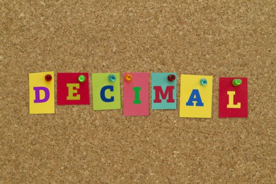 The word 'Decimal' written on sticky notes pinned to a corkboard