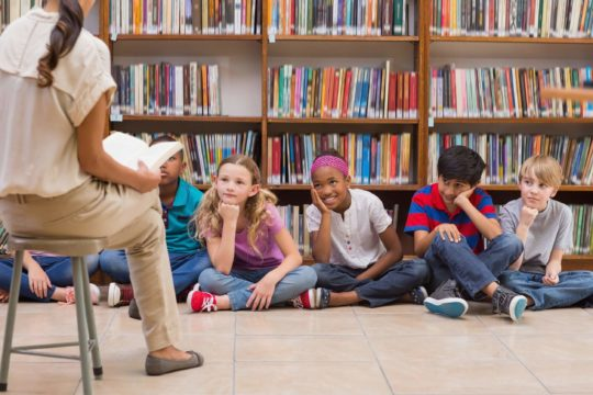 A school librarian reads a book to a group of children in the library.