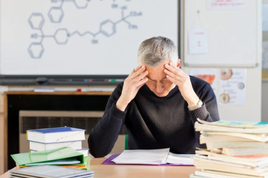 A stressed science teacher tries to grade homework in a classroom.