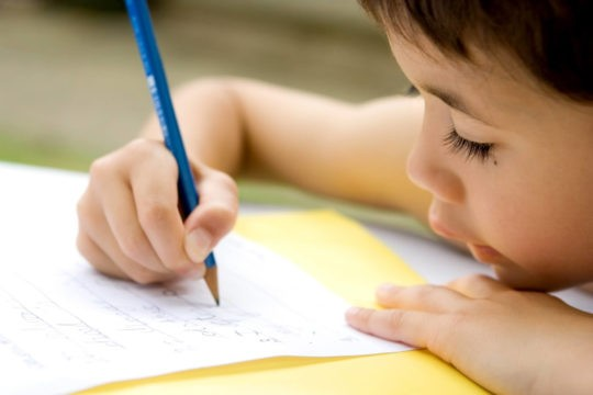Young boy does writing as part of his homework.