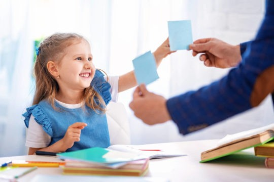 A girl chooses between two post-it notes that her teacher is showing her.