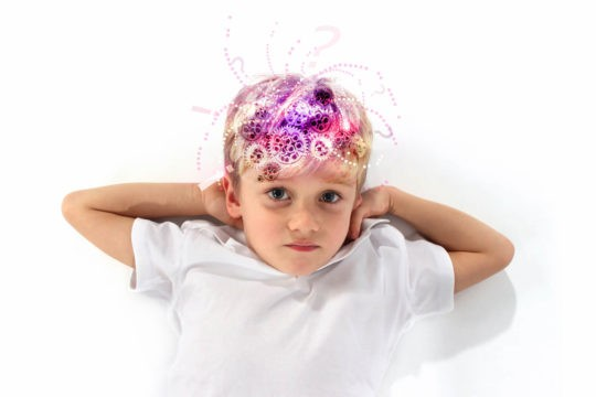 """A boy lays on the ground, showing the """"gears turning"""" in his head as he thinks."""