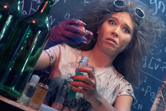 A young girl holds a science flask, doing Halloween experiments.