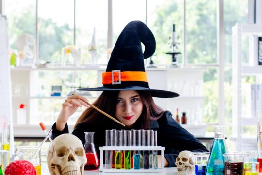 A girl in a witch costume sits in a science lab surrounded by lab experiment equipment.