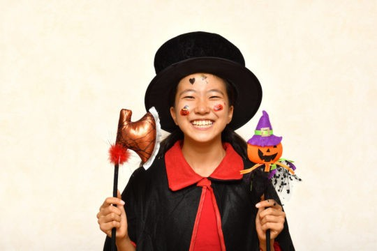 A girl dressed in a costume with a top hat smiles at the camera, holding a Halloween decoration.